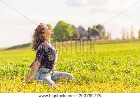 Portrait Of Young Smiling Woman Sitting In Yellow Dandelion Farm Field At Sunset By House In Ile D'o