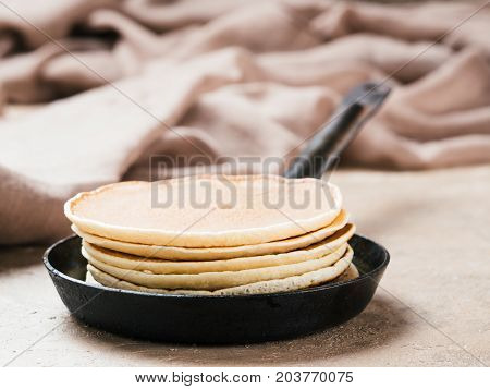 homemade pancakes in iron cast. Stack of pancakes on brown concrete background. Close up.