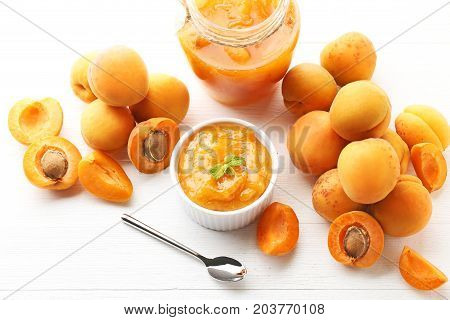 Apricot Jam In Bowl And Glass Jar With Spoon On White Wooden Table