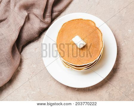 Top view of homemade pancakes. Stack of pancakes on brown concrete background.