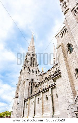 Sainte-Anne-de-Beaupre Canada - June 2 2017: Exterior stone architecture of Basilica of Sainte Anne de Beaupre with cross spire against blue sky