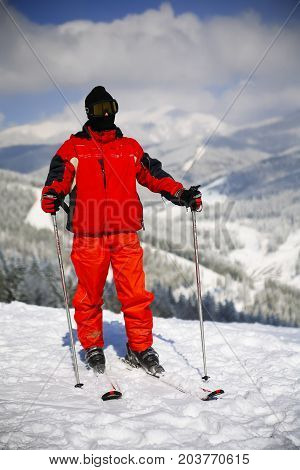 Young active man skiing in mountains. Male skier with goggles and poles enjoying sunny winter day in Swiss Alps. Ski race for adults. Winter and snow sport in alpine resort.
