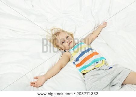Little boy lying in the white bed