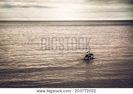 Sailing boat sail away into  the sea towards horizon during sunset with copy space in purple toned colors symbolizing beginning of a long journey