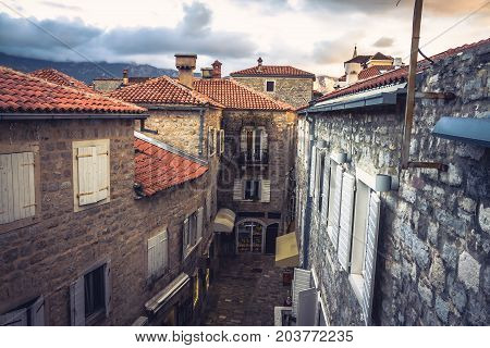 Vintage european city street  with orange tile roofs and ancient building facade in front of dramatic sunset sky with antique architecture in old European town Budva in Montenegro