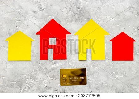 work desk with paper house figures for selling house set stone background top view