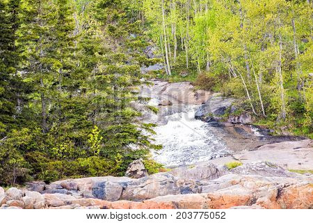 Inland Creek Flowing Down Rocky Cliff In Port-au-persil, Quebec, Canada In Charlevoix Region To Sain