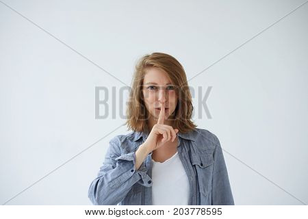 Silence secret conspiracy confidential information and taboo concept. Portrait of mysterious young European woman dressed casually saying shh holding finger on her lips asking to keep silent