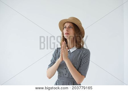 Desperate young European female crying and begging for mercy keeping palms pressed together in prayer having unhappy and mournful expression on her face looking up asking for forgiveness