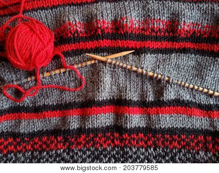 Red yarn ball, knitted wool garment and wooden needles for knitting