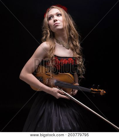 Blond beautiful girl in red wreath with violin on black background