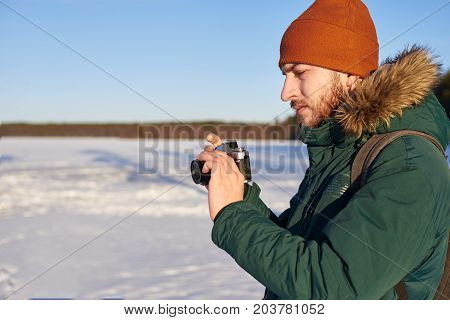 Portrait of serious unshaven young Caucasian adventurer in winter hat and coat setting up his digital photo camera while spending Christmas holidays in wild nature enjoying beautiful snowy views