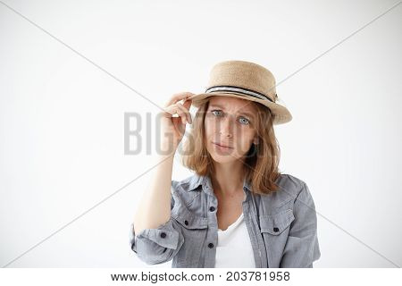 Clothing syle and fashion concept. Lifestyle picture of attractive young European woman with blue eyes and short fair hair posing at white studio wall holding hand on her stylish round hat