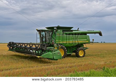 MOORHEAD, MINNESOTA, August 14, 2017: The self propelled green combine combine parked in the stubble of a wheat field is a product of John Deere Co