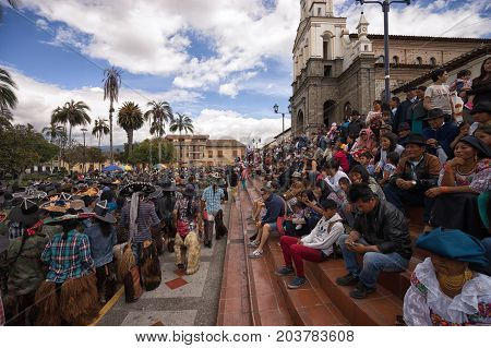 June 25 2017 Cotacachi Ecuador: spectators stting on the stairs of the church in the main plaza watching the Inti Raymi parade