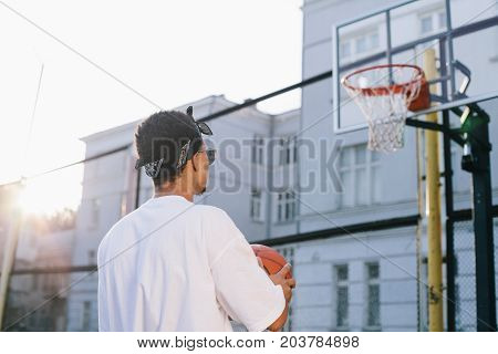 Well-built and young man is standing at the small stadium and looking up to the basket. He is holding tha ball in his hands. This guy is ready to start the game. Close up. Cut view