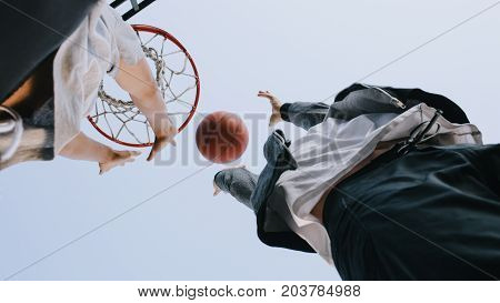 Cut view of a game which two friends are playing. They are in the action of catching the ball that is falling down. Close up