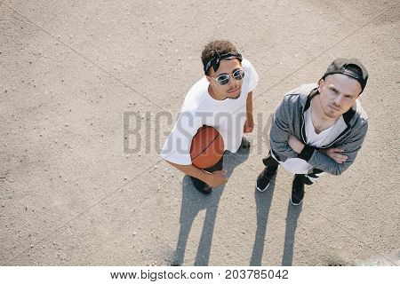 Two basketball players are standing on the red playground in a sunny day. One of them is holding the ball in his hand while the other one is keeping his hands crossed. They are looking up to the camera. The sight of young men is serious and fearless.
