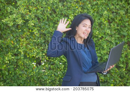 businesswoman holding computer notebook and showing making the glad gesture.