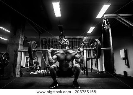 Strong muscular man at a cross fit gym lifting a barbell.