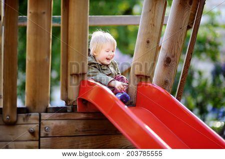 Happy Little Boy Having Fun On Outdoor Playground
