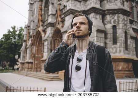 Close view of a young hipster that likes to travel. He is standing near a building and talking on the phone. It's chilly outside so that's why he wears a sweater and a hat.