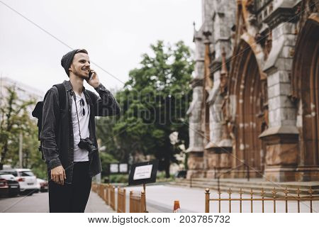 The photo of a traveller standing on the sidewalk near the old church in a big town. He is standing toward the building and talking on the phone. He is smiling to himself and looking straight forward.