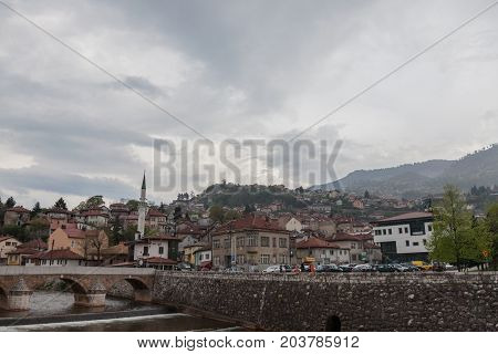 SARAJEVO BOSNIA AND HERZEGOVINA - APRIL 15 2017: Panorama of the left bank of Sarajevo in the old part of the city during a cloudy and rainy afternoon of spring. Sarajevo is the capital city of Bosnia and Herzegovina