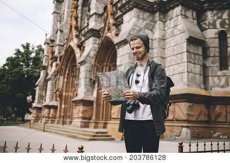 Young and ambitious tourist is standing on the sidewalk near the cathedral and reading a map. The guy was lost but now he has finally found his current location. So that's why he is so happy.