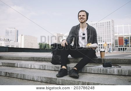 The traveller is sitting on the steps. He is holding a plate with his snake in one hand. The other one is laying down on his knee. On the left we can see his black backpack. On the right side there is a camera and cup of coffee. The guy is really happy.
