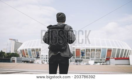 The picture of traveller that is standing on the big square and looking to the big white stadium. He has finally finished the trip and it's time to go home. But he knows he will come back to this city again.