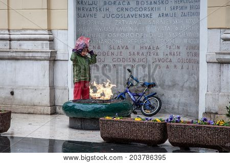 SARAJEVO BOSNIA AND HERZEGOVINA - APRIL 16 2017: Young roma girl trying to warm up in the rain in front of the eternal flame of a WWII monument in the center of Sarajevo. Roma people are vamong the poorest communities of Balkans
