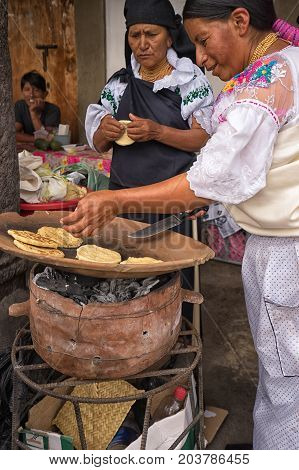June 25 2017 Cotacachi Ecuador: quechua women preparing flatbreads made of corn during Inti Raymi festival on the side of the street