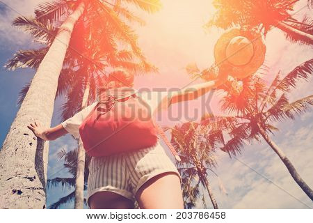 Young and happy girl with outspread hands enjoying holidays in nature resort intentional sun glare and vintage color