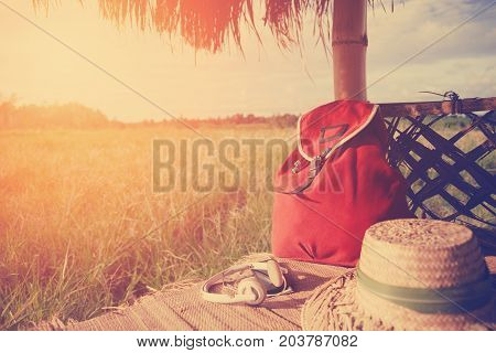 Mobile phone, headphones, hat and backpack in nature intentional sun glare and vintage color