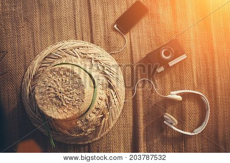 Mobile phone, film photo camera, headphones and hat lying outdoors intentional sun glare