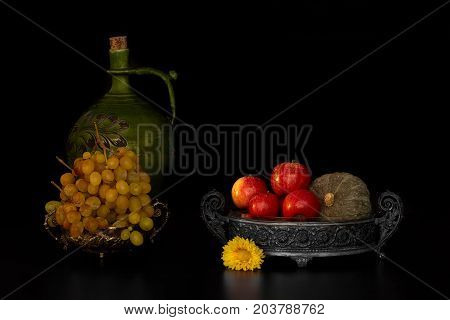 Autumnal still life with apples grape and pumpkin on black background.
