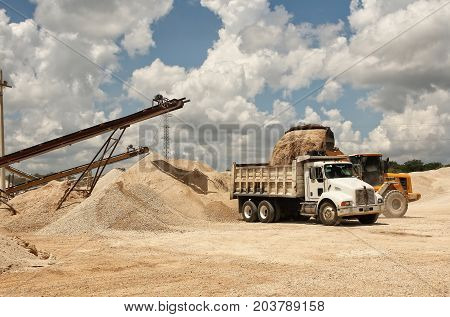 An image of a quarry where you can see the transport bands of stone material already sprayed being placed by a retro digger towards a truck to transport color daylight