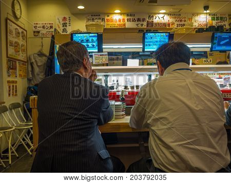 TOKYO, JAPAN -28 JUN 2017: Unidentified people eating an assorted japanesse food over a table, inside of a kaitenzushi conveyor belt sushi restaurant, in Tokyo, Japan.