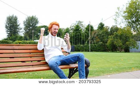 Man Excited For Successs, Using Smartphone, Sitting On Bench