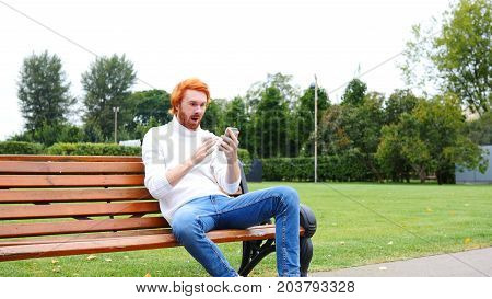 Amazed Man Excited For Successs, Using Smartphone, Sitting On Bench