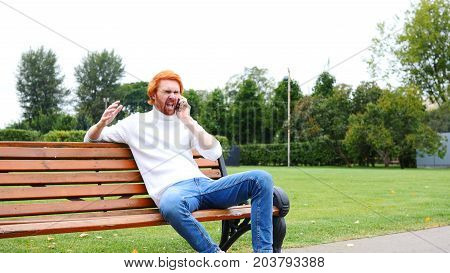 Screaming Angry Man Attending Phone Call In Park, Red Beard And Hairs