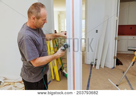 Carpenter Using A Brad Nail Gun To Complete Framing Trim Air Gun For Nailing