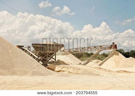An image of a quarry where you can see the transport bands of stone material already crushing in different grades of pulverized which is being stacked for transfer color daylight