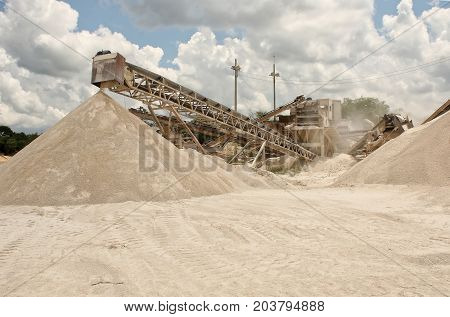 An image of a quarry where you can see the conveyor belt of stone material already crushed which is being stacked for transfer to the bottom crusher machine color daylight blue sky and clouds background