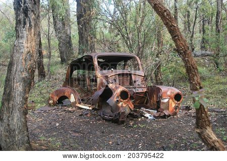 wrecked rusty rustic car in nature left behind