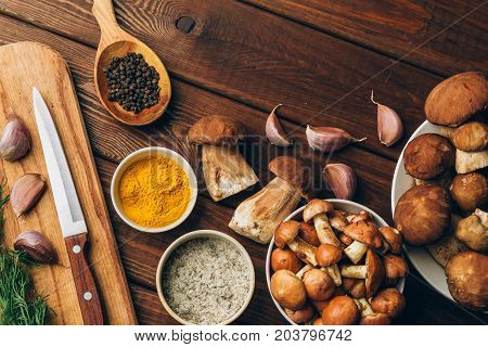 Ingredients for mushroom soup, mushrooms, garlic, spices on wooden table, top view, copy space. Autumn dinner and healthy organic food concept