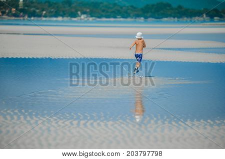 Seven Years Old Boy Runnig Along The Shallow On The Desert Sunny Beach