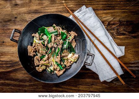 Traditional Chinese Mongolian Beef Stir Fry In Chinese Cast Iron Wok With Cooking Chopsticks, Wooden