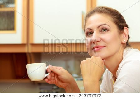 Pensive mature woman holding cup of coffee in kitchen. Housewife female with hot energizing beverage. Caffeine energy.